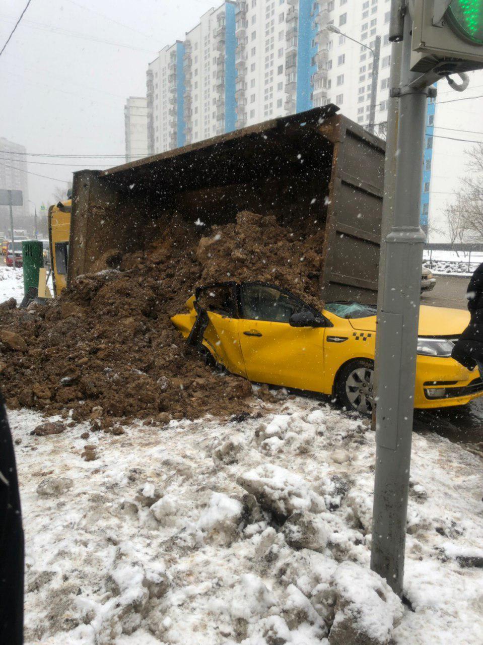 Груженный песком КамАЗ опрокинулся на такси в Москве